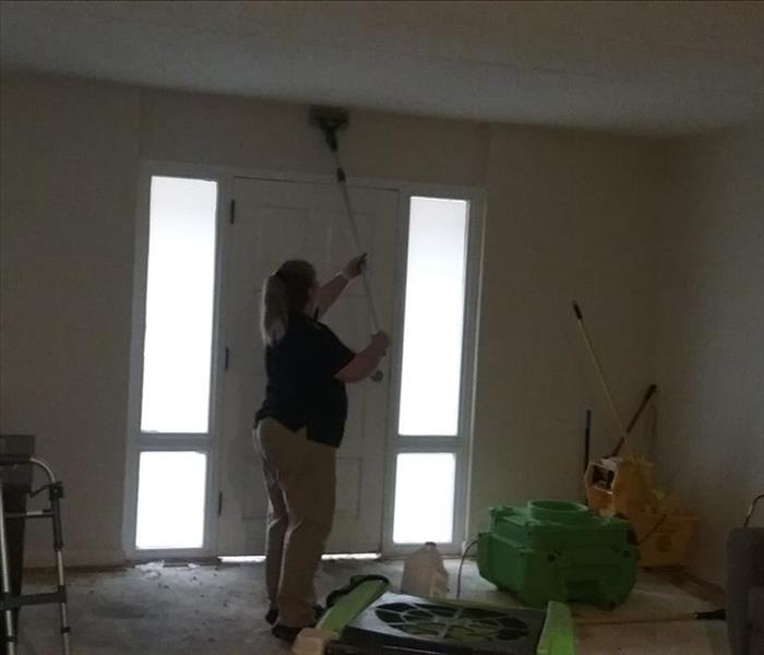 Sponging a ceiling affected by soot and smoke